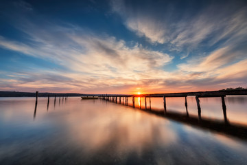 Lake sunset. Magnificent long exposure lake sunset with boat and a wooden pier