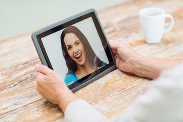 senior woman with photo on tablet pc at home