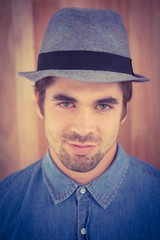 Close-up portrait of confident hipster wearing hat