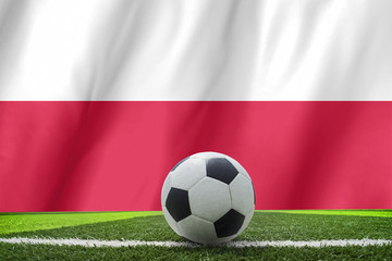 Soccer ball and national flag of Poland lies on the green grass