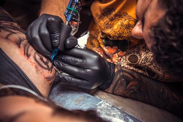 Tattoo master at work in tattoo studio