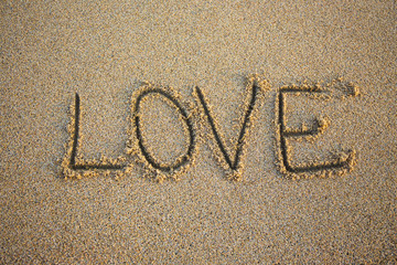 close up of word love written in sand