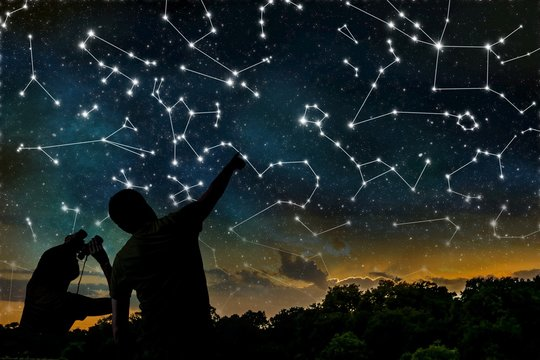 Astrology concept. Constellations on night sky. Silhouettes of astrologers observing zodiac constellation.