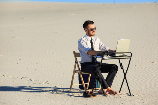 Businessman using  laptop in a desert