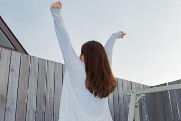 外で背伸びをするパジャマ姿の女性