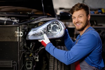 Mechanic with new car headlight in a workshop Wall mural