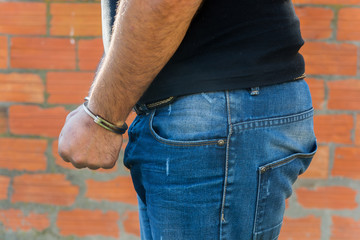 Man with Handcuffs in front of terracota brick block wall, left hand side view