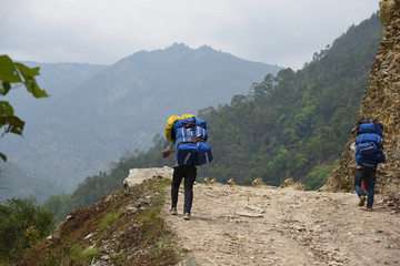 the porter is carrying stuff to trek to Poonhill, Nepal