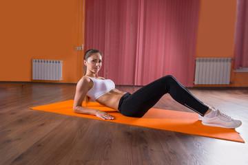 Young Woman Reclining on Floor Mat in Dance Studio
