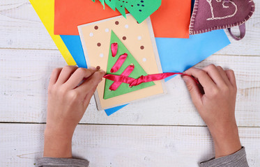 Close up on child's  hands making Christmas Tree from colored paper.   Kids Art, Art Projects, Handmade New Year decorations
