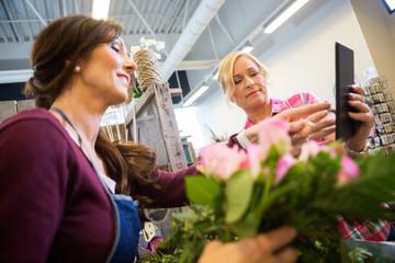 Customer Showing Something On Digital Tablet To Florist