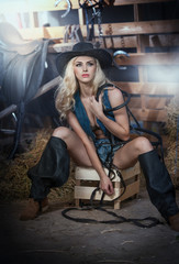 Beautiful blonde girl with country look, indoors shot in stable, rustic style. Attractive woman with black cowboy hat and denim shorts