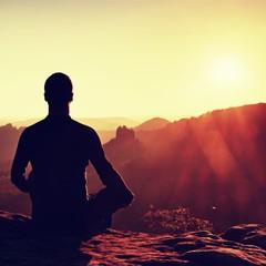 Hiker in squatting position on a rock, enjoy dybreak  scenery