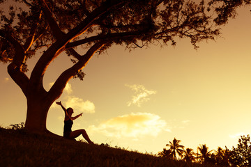 Silhouette of woman with hands raised into the sunset