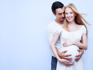 Image of pregnant couple. Husband touching his wife belly with hands