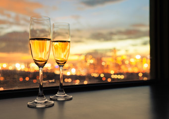 Glasses of champagne against city sunset.
