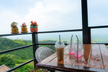 Iced coffee in plastic cup in coffee shop with mountain view