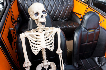 Laughing skeleton as a passenger in an old car ready for the Day of the Dead or Dia de los Muertos