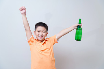 Asian boy drinking water from green bottle