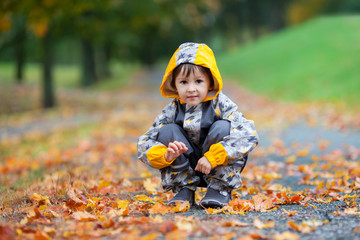 Little boy, playing in the rain in autumn park