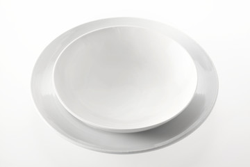 Empty Bowl on a Round Plate Against White