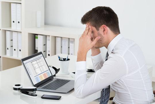 Businessman Suffering From Headache At Desk