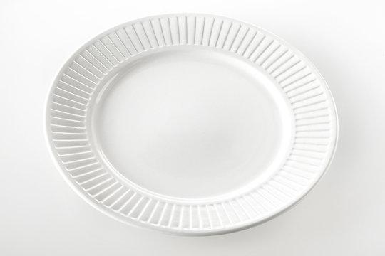 Empty white dinner plate with ridged rim