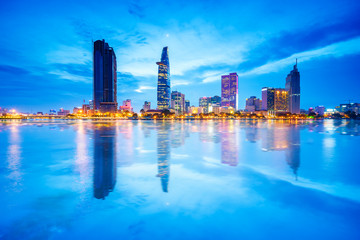 Reflection of night view of Business and Administrative Center of Ho Chi Minh city on Saigon riverbank, Vietnam. Ho Chi Minh city (aka Saigon) is the largest city and economic center in Vietnam.