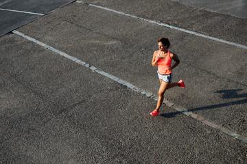 Top view of woman running on city asphalt. Female runner training outdoor.