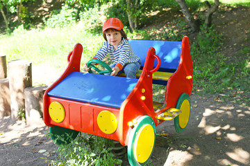 Little child drives car on playpit