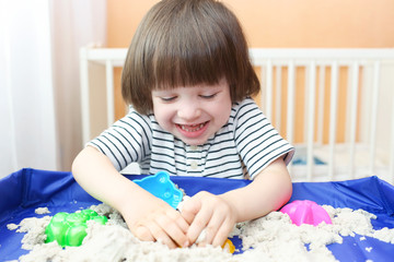 Happy smiling child plays kinetic sand at home