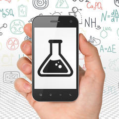 Science concept: Hand Holding Smartphone with Flask on display