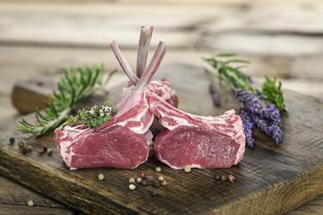 Rohes Lammfleisch als Lammkarree auf edlem Holzbrett