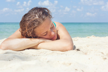 beautiful young woman lying on the sand on the shore of the warm
