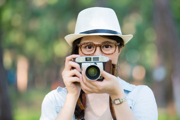 Beautiful young girl with retro camera photographing, outdoor