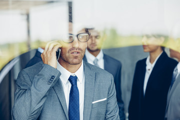 Businessman on cell phone behind window with colleagues in background
