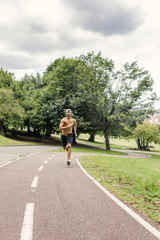 Athletic young man jogging in the park