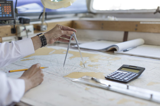 Deck officer working on a nautical map