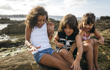 Spain, Gijon, group picture of three excited little children sitting at rocky coast