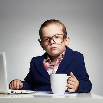 Young business boy. funny child in glasses. little boss in office