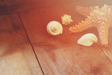 photo of vintage decorative boat, sea shells and starfish on wooden old table. retro filtered image. marine background