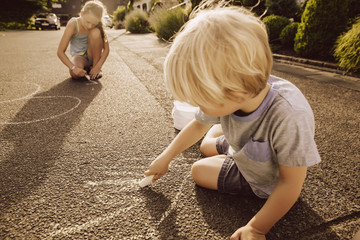 Children using sidewalk chalk in their neighborhood