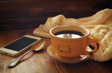 Cup of tea with smartphone on wooden table