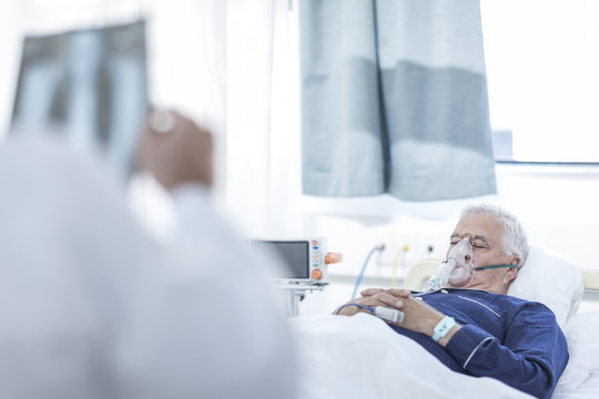 Senior man with oxygen mask lying in a hospital bed