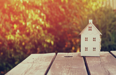 small house model over wooden table outdoors at garden . filtered image. selective focus