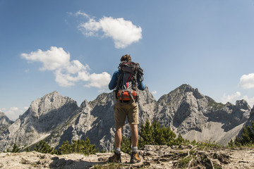 Austria, Tyrol, Tannheimer Tal, young man standing on mountain trail looking at view