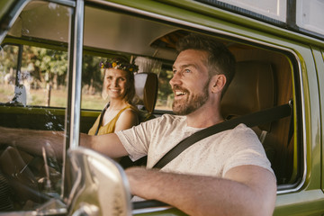 Smiling couple in van on a road trip