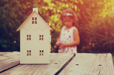 small house model over wooden table outdoors at garden and kid playing. selective focus . filtered image