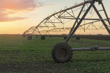 Modern irrigation system on a farm field at sunset.