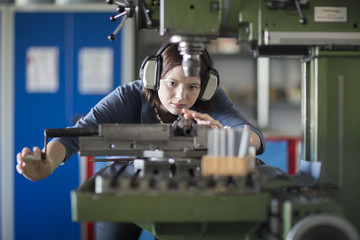 Young woman with ear protectors working at machine